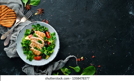 Salad with chicken fillet, olives, tomatoes and avocados in a plate on a wooden background Top view. Free space for your text. Flat lay