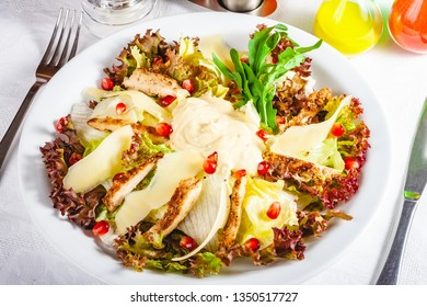 Salad with chicken, greens mix and parmesan cheese on white plate. Close up