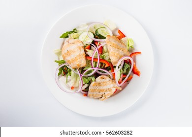 salad with chicken on a white plate on a light background (close top view)