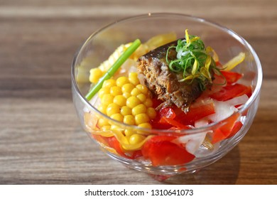 The salad of chopped Saury fish or called Sanma in Japanese with fresh corns, sliced onion and vegetable in the transparent bowl.