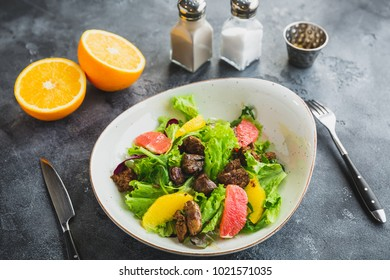 Salad with citrus, lettuce and grilled chicken liver in a plate.