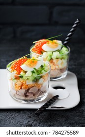 Salad of cod liver with eggs, cucumbers and red caviar in a glass, selective focus