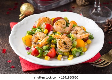 Salad with corn, fried shrimp, cherry tomatoes, red onions and lettuce on  white plate. Appetizer for Christmas party on dark background