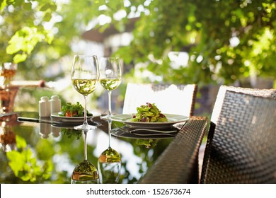 A salad and a couple wineglasses on a table outdoor with hookah on the background