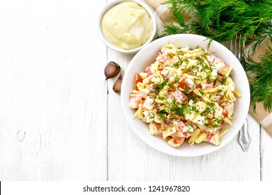 Salad of crab sticks, cheese, garlic, eggs and tomatoes, dressed with mayonnaise in a plate, napkin and parsley on a wooden board background from above