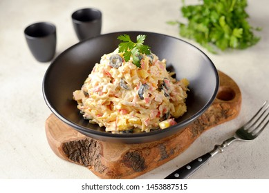Salad of crab sticks with pineapple, cheese, boiled eggs and olives.