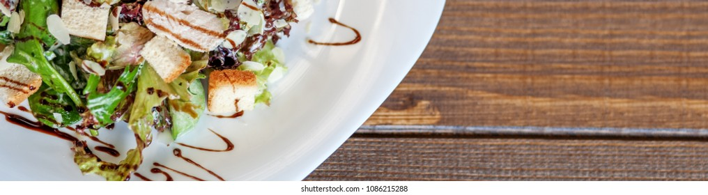Salad with cucumber and chicken and lettuce on a wooden background. Banner for website. The concept of food and diet.