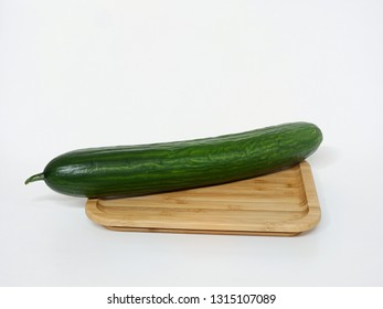 Salad cucumber on a wooden board, isolated against a white background.
