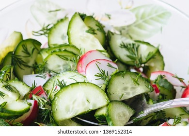 Salad cucumber radish dill in plate with spoon close up
