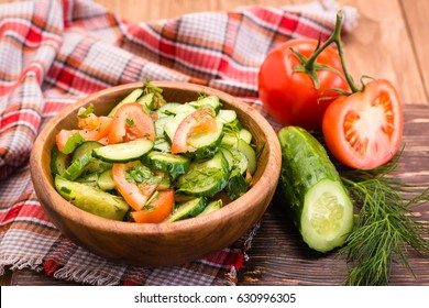 Salad of cucumbers and tomatoes in a wooden plate and vegetables on a table