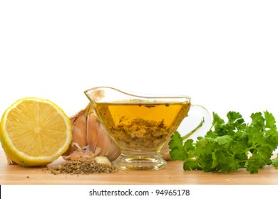 salad dressing with olive oil, garlic and lemon over white background