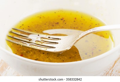 Salad dressing in a white bowl. Selective focus