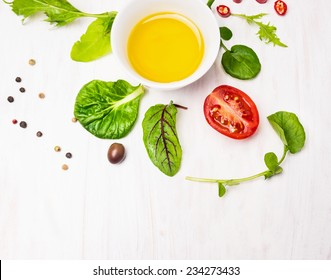 Salad  with dressing,olives and tomatoes on white wooden background, top view