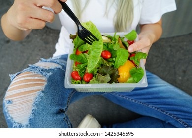 Salad eating moment, hand using black plastic fork to eat Romaine Lettuce from bioplastic take out packaging contained mixed vegetables salad added tomatoes and yellow bell pepper. (selective focus)