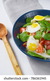 Salad with eggs, tomato and spinach in a plate with a wooden spoon
