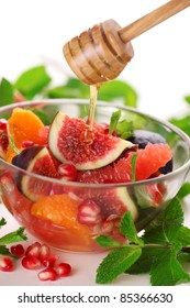 salad with figs, grapefruit, tangerine and pomegranate with wooden stick honey.