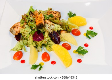 Salad with fish, vegetables and greens on a white plate