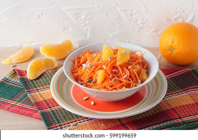 Salad of fresh carrots with orange slices and sunflower seeds in bowl
