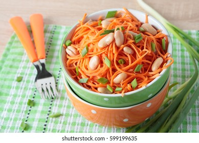 Salad of fresh carrots with white beans and green onions in a bowl