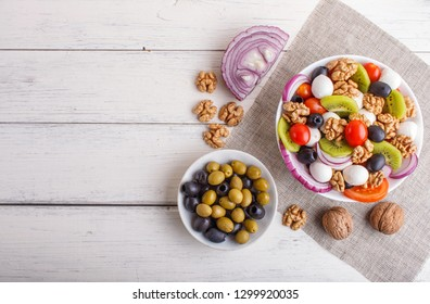 Salad with fresh cherry tomatoes,  mozzarella cheese, olives, kiwi, onion and walnuts on white wooden background, copy space, top view.