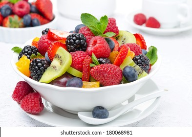 salad of fresh fruit and berries in a white bowl, berries and a cup of tea in the background, horizontal