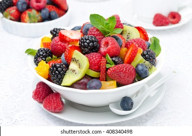 salad of fresh fruit and berries in a white bowl, berries and cup of tea in the background, closeup