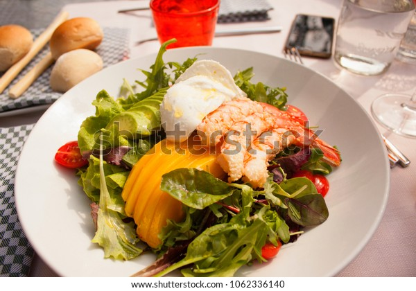 Salad of fresh greens, shrimps, mango, mozzarella, tomatoes and avocado on a white plate