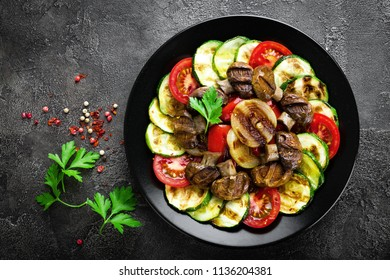 Salad with fresh and grilled vegetables and mushrooms. Vegetable salad with grilled champignons. Vegetable salad on plate