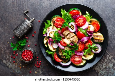 Salad with fresh and grilled vegetables and mushrooms. Vegetable salad with grilled champignons. Vegetable salad on plate. Healthy vegetarian food