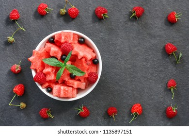 Salad of fresh juicy pieces of watermelon, raspberry and currant with green mint leaves on black stone countertop