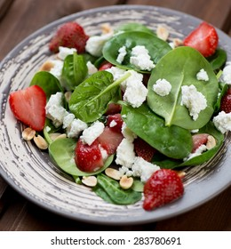 Salad with fresh spinach, strawberries, cheese and peanuts, close-up