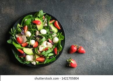 Salad with fresh strawberries, arugula, basil, avocado and mozzarella on a dark background top view copy space.