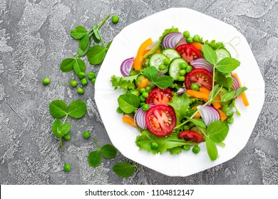 Salad. Fresh vegetable salad with tomato, onion, cucumbers, pepper, lettuce and green peas. Vegetarian salad with vegetables on plate