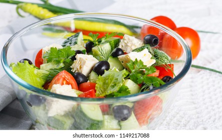 Salad of fresh vegetables and cheese on  served table with pepper, green onions and tomatoes
