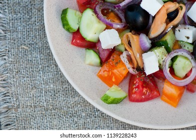 Salad from fresh vegetables, cheese and seafood.