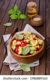 Salade de légumes frais avec pois chiches à l'huile sur fond bois. Mise au point sélective.