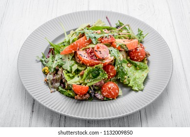 Salad with fresh vegetables with dried tomatoes, meat and mustard. On a wooden table