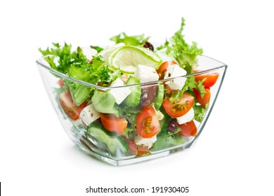Salad with fresh vegetables in a glass bowl isolated on white background