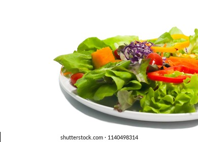 Salad and fresh vegetables isolated on white background.