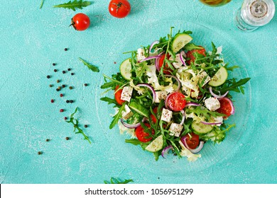 Salad of fresh vegetables - tomato, cucumber and feta cheese in Greek style. Flat lay. Top view
