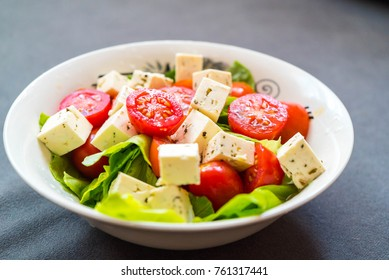 Salad of fresh,colored cherry tomatoes with greek feta chese.  Fresh salad. Green salad, cherry tomatoes, goat cheese. Salad with cheese and fresh vegetables