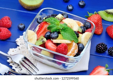 Salad with fruits in a bowl on a wood table