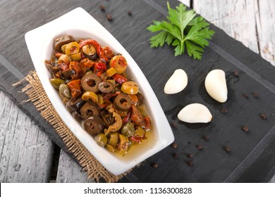 Salad or giardiniera made from green olives, black olives, olive oil, celery, cauliflower, carrots, sweet peppers, onions, capers, parsley, pepperoncini, oregano, garlic, vinegar, herbs and spices.