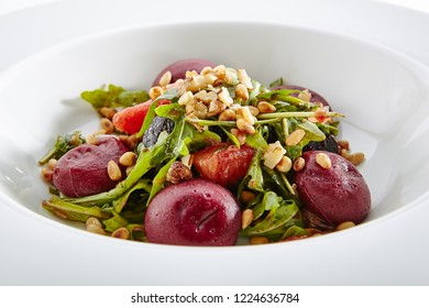 Salad with Grapefruit Pine Nuts and Arugula Garnish with Beets Hemispheres Isolated on White Background. Restaurant Exquisite Serving Dish with Fruit and Vegetables Salat Close Up