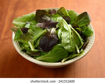 Salad greens in a bowl on a wooden table.