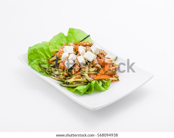 Salad with greens, tofu and bell peppers on white plate