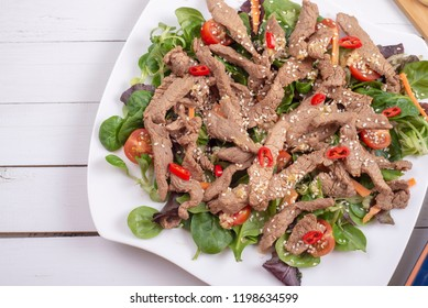 Salad with grilled beef, lamb's lettuce, tomatoes and chilli on a plate and chopsticks. Asian style. Top view. Copy space