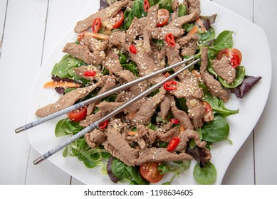 Salad with grilled beef, lamb's lettuce, tomatoes and chilli on a plate and chopsticks. Asian style. Top view