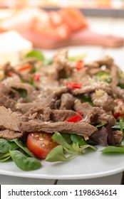 Salad with grilled beef, lamb's lettuce, tomatoes and chilli on a plate and chopsticks. Asian style.