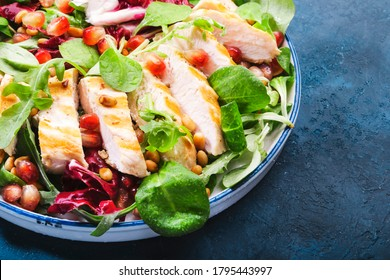 Salad with grilled chicken, spinach, arugula, cedar nuts and pomegranate seeds. Healthy food and eating concept. Top view. Blue background